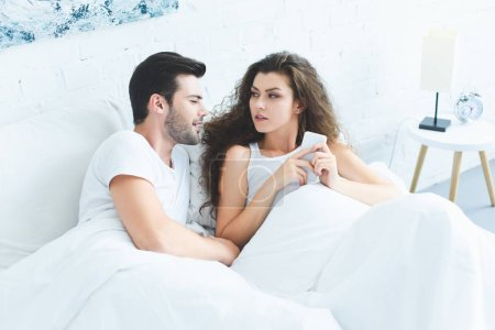 high angle view of smiling young man looking at girlfriend using smartphone in bed
