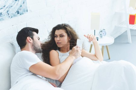 young couple holding smartphone and quarreling in bed, relationship difficulties concept