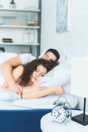 close-up view of alarm clock and young couple sleeping in bed behind