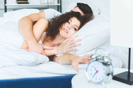 Photo for Sleepy young woman reaching for alarm clock while boyfriend sleeping in bed - Royalty Free Image