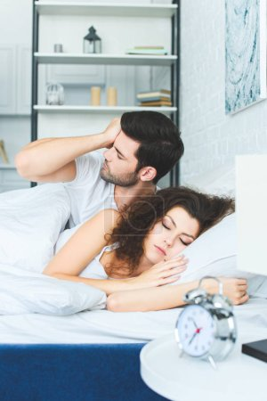 young man waking up and rubbing eye while girlfriend sleeping in bed
