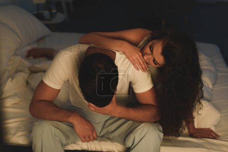 Photo for Young woman looking at upset boyfriend sitting on bed at night, relationship difficulties concept - Royalty Free Image