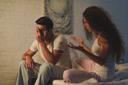 emotional young woman quarreling with upset boyfriend on bed, relationship difficulties concept