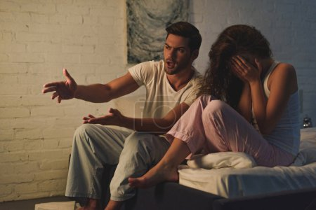 young couple in pajamas quarreling on bed, relationship difficulties concept