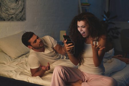 angry young woman using smartphone and screaming while boyfriend lying on bed at night