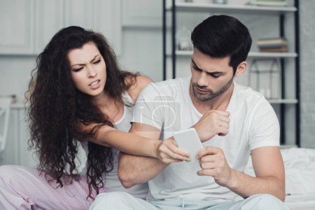 upset young couple holding smartphone and quarreling, relationship difficulties concept