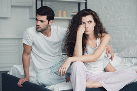 dissatisfied young couple in pajamas having quarrel on bed, relationship difficulties concept