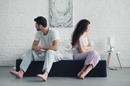 Photo pour Bouleversé de jeune couple en pyjama assis avec les bras croisés sur le lit, notion de difficultés de relation - image libre de droit
