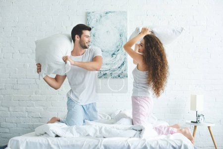 Photo for Side view of happy young couple in pajamas fighting with pillows on bed - Royalty Free Image