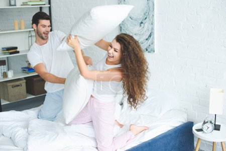 happy young couple in pajamas fighting with pillows on bed