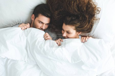 top view of happy young couple lying under white blanket in bed