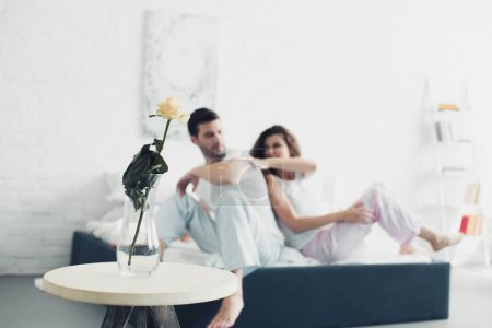 rose flower in vase and young couple quarreling on bed behind