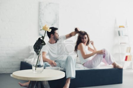 rose flower in vase and couple quarreling on bed behind, relationship difficulties concept