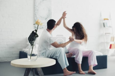 rose flower in vase and young couple quarreling on bed behind, relationship difficulties concept