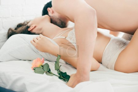 man holding rose flower and kissing sexy girlfriend in bed