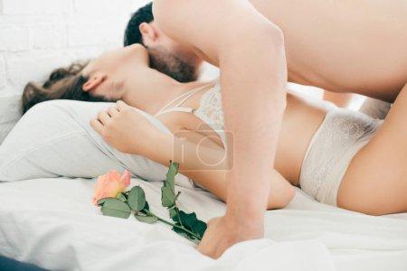 Photo pour Homme tenant rose fleur et embrasser sexy copine dans le lit - image libre de droit