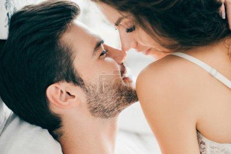 Photo pour Vue rapprochée du séduisant jeune couple heureux capable d'embrasser préliminaires - image libre de droit