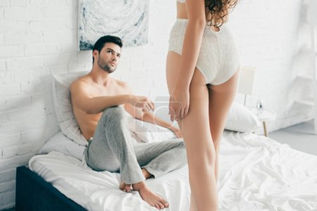 Photo for Cropped shot of handsome man looking at seductive girlfriend in lingerie standing on bed - Royalty Free Image