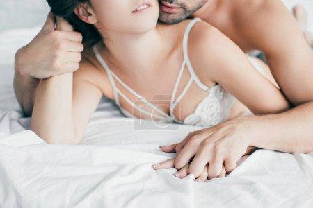 Photo pour Plan recadré de jeune couple sexy tenant la main dans les préliminaires sur le lit - image libre de droit