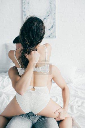 Photo pour Couple jeune passionné en sous-vêtements caresses préliminaires sur le lit - image libre de droit