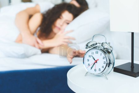 close-up view of alarm clock and young couple waking up in bed