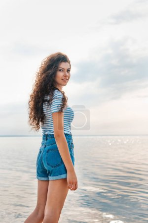beautiful curly woman posing on seashore