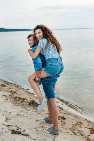 cheerful young couple piggybacking on beach near sea