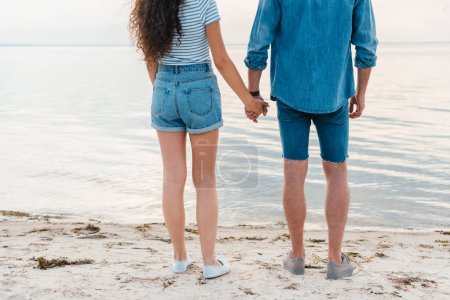 cropped view of couple holding hands and standing near the sea