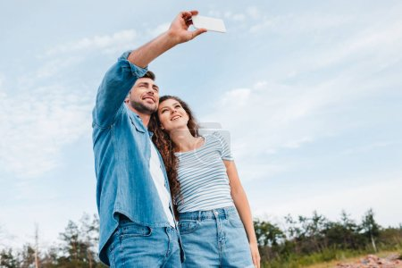 bottom view of beautiful couple taking selfie on smartphone
