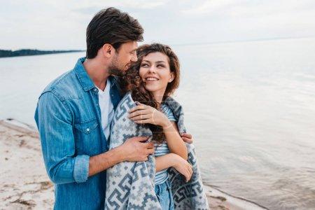 boyfriend embracing smiling girlfriend wrapped in blanket near sea
