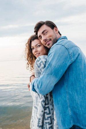 happy man hugging girlfriend wrapped in blanket