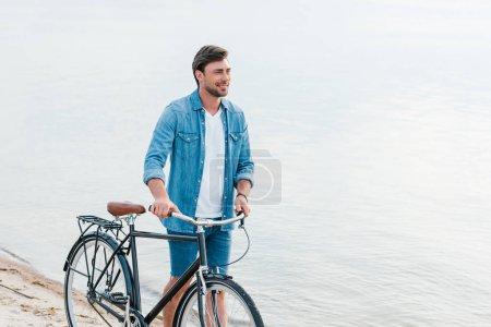 handsome man walking with bike on sand beach
