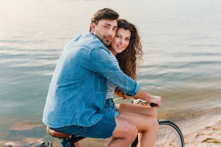 couple sitting on bicycle on beach near sea and looking at camera