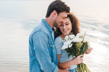 smiling couple embracing and holding bouquet near the sea