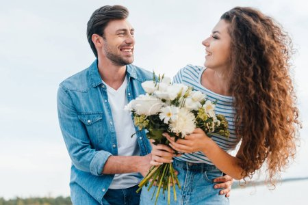happy couple hugging and holding bouquet together near the sea