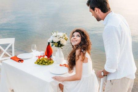 beautiful happy couple having romantic date on seashore