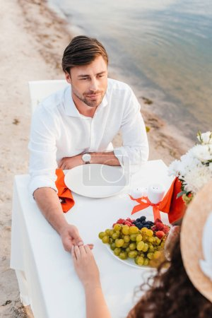 beautiful couple holding hands on romantic date on seashore