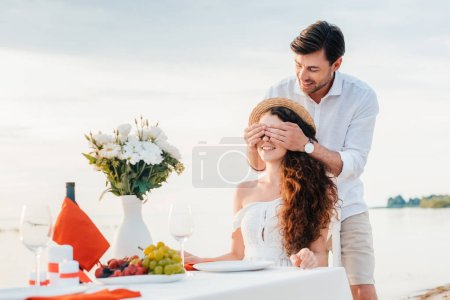 handsome happy man closing eyes and making surprise for girlfriend, romantic date on seashore