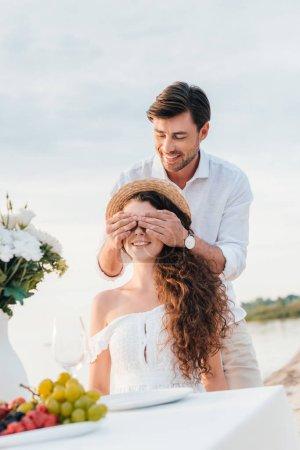 homme souriant, fermant les yeux et faire la surprise pour petite amie, un rendez-vous romantique au bord de mer