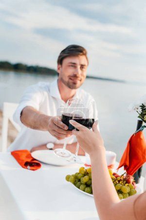 couple clinking with wineglasses during romantic date on seashore