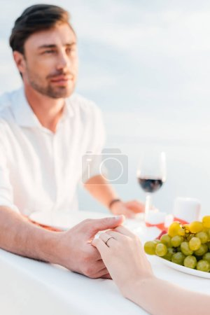 young couple holding hands after propose in romantic date