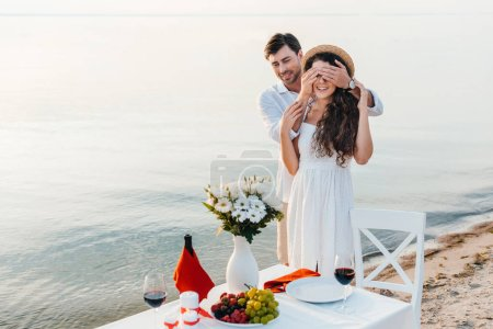 happy man closing eyes and making surprise for girlfriend, romantic date near sea
