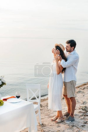 young man closing eyes and making surprise for girlfriend, romantic date on beach