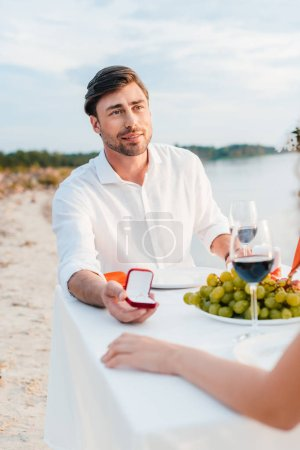 handsome man making propose with ring to woman in romantic date on beach