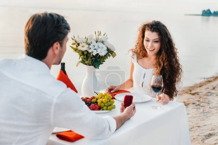man making propose with ring to attractive woman in romantic date outdoors