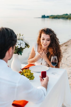 Photo for Man making propose with ring to excited girl in romantic date outdoors - Royalty Free Image