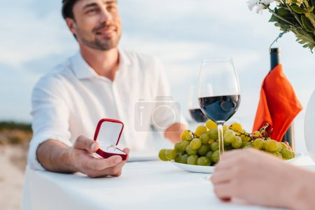 happy man making propose with ring to girlfriend in romantic date