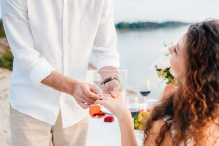 vue recadrée de l'homme portait la bague sur le doigt de womans après proposent sur rendez-vous romantique
