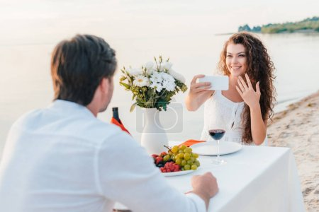 happy woman taking selfie with proposal ring on finger