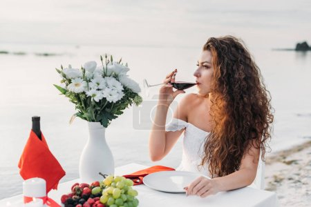 beautiful curly woman drinking wine on romantic date on seashore